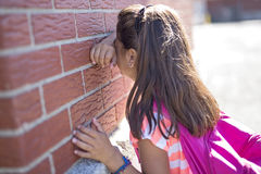Six years old school girl cry beside brick wall. A six years old school girl cry beside brick wall royalty free stock image