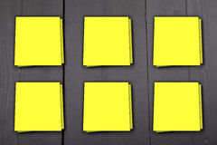 Six yellow memo notes on black wooden background Stock Images