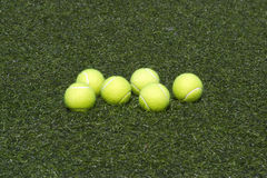 Six yellow tennis balls lays on grass Stock Images