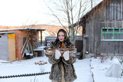 At sixes and sevens, inharmoniously. Girl with firewood. Russian village. Winter.Canon 5Dmark2 Royalty Free Stock Photos