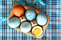 Sixpack av kulöra dekorerade påskägg på den rutiga blåa bakgrunden arkivfoton