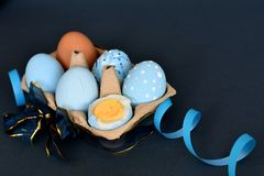 Sixpack of light blue colored Easter eggs decorated with ribbons. Six hard boiled colored eggs in a carton pack. Painted light blue, one is brown natural color royalty free stock photo