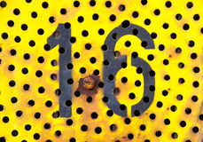 Sixteen 16. A sixteen on a rusty and old yellow background, full of little holes Stock Photo