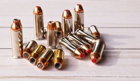 Sixteen bullets, eight 40 caliber hollow points and eight 44 special red tipped ones. On a white wooden background royalty free stock image
