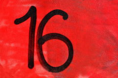 Sixteen. Number 16 sixteen painted with black graffiti paint on red background of the textured wall Stock Images