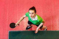 Sixteen year old Caucasian teen girl holding a ping pong paddle, top view. Sixteen year old Caucasian teen girl holding a ping pong paddle indoors, top view stock image