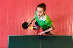 Sixteen-year-old Caucasian teenage girl to play ping pong, view from above. Sixteen-year-old Caucasian teenage girl to play ping pong indoors, view from above stock photos