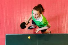 Sixteen-year-old teen girl makes a serve of the ball in table tennis, top view. Teens and ping pong. Sixteen-year-old teen girl makes a serve of the ball in royalty free stock photo