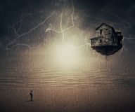Sixth sense. Surreal backround of a man standing in the rain, in front of a flying house ripped from the ground, near the ocean. Sixth sense concept Royalty Free Stock Image
