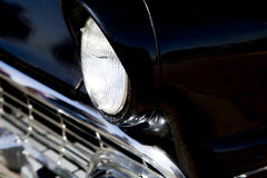 Sixties classic black car front end close up. Sixties classic black car front end head light and bumper Royalty Free Stock Photos