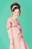 Sixties Fashion. Woman in sixties style fashion posing with wink. Pink and cyan retro colors. Sixties hairstyle Stock Images