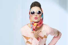 Sixties Style Girl. Blowing a kiss. Retro fashion with silk scarf and sunglasses Stock Images