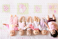 Sixtuplets. A real baby among five baby dolls Stock Photos