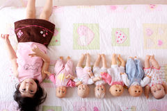 Sixtuplets. A real baby among five baby dolls Royalty Free Stock Photos