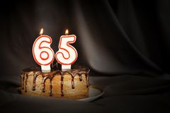Sixty five years anniversary. Birthday chocolate cake with white burning candles in the form of number Sixty five. Dark background with black cloth royalty free stock images