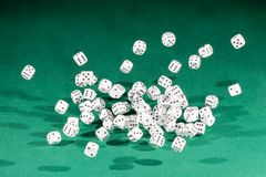 Sixty white dices falling on a green table stock image