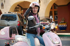 Sixty year old biker. Female biker pulling her visor down as she prepares to ride on her scooter Royalty Free Stock Images