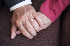 Sixty year old man and woman's hands holding each other Royalty Free Stock Photography
