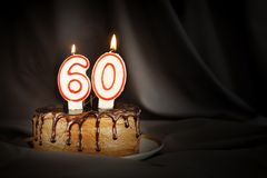 Sixty years anniversary. Birthday chocolate cake with white burning candles in the form of number Sixty. Dark background with black cloth stock image