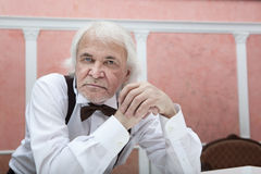 Sixty years gray-haired man in a white shirt and bow tie Royalty Free Stock Photos