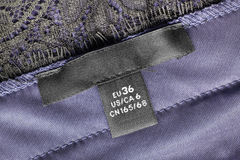Size clothes label. Black clothes size label on purple satin as a background Royalty Free Stock Photography