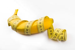 Size matters concept, banana with measuring tape Royalty Free Stock Photo