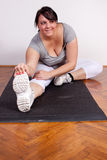 Size plus woman stretching on the floor Royalty Free Stock Photography