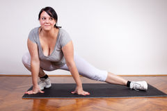 Size plus woman stretching on the floor Royalty Free Stock Image