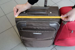 Sizes. A suitcase and a measuring tape Stock Image