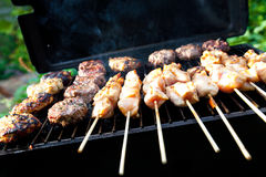 Sizzling burgers and chicken kebabs. On hot barbecue outdoor Stock Photo