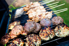 Sizzling burgers and chicken kebabs. On hot barbecue outdoor Stock Photos