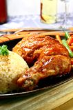 Sizzling chicken. Chicken leg served on a hot iron plate stock photo