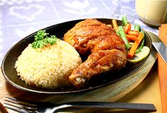 Sizzling chicken. Chicken leg with rice served on a hot iron plate royalty free stock photo