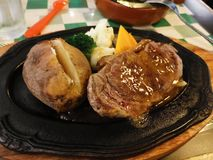 A sizzling hot plate of beef steak. Medium, rare, potato, baked, vegetables, broccoli, meal, dish, cow, meat, red stock images