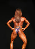 Sizzling Hot Redheaded Woman Bodybuilder Rear Pose Stock Image