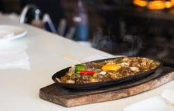 Sizzling pork sisig with raw egg Stock Image