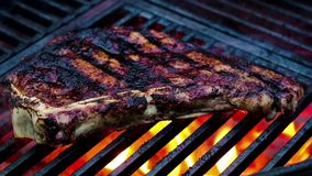 Sizzling steak with grill marks on iron grates, smoke and flames billow from hot charcoal stock video