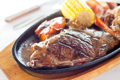 Sizzling Steak. Grilled beef steak served on a hot sizzling plate with sweet corn, tomatoes, big prawns and brown sauce Stock Image