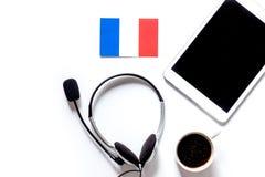 Själv-utbildning Lära franskt online- Hörlurar och minnestavlaPC på vit copyspace för modell för bästa sikt för tabellbakgrund royaltyfri bild