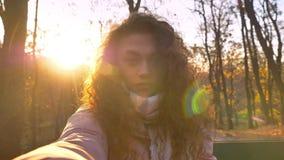 Själv-videoen av den caucasian lockig-haired kvinnan i solsken som gör selfie-foto i höstligt, parkerar stock video