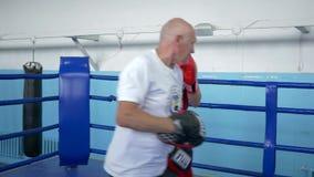 Självförsvarutbildning, idrottsman utför boxningstansmaskiner, medan utbilda med lagledaren för strid på cirkeln på sportar lager videofilmer