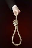 Självmord- och affärsämne: Hand av en affärsman i ett svart omslag som rymmer en ögla av det isolerade repet för att hänga på mör royaltyfri bild