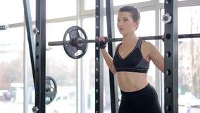 Självsäker härlig dam som squatting med skivstången som hårt arbetar för att nå mål arkivfilmer