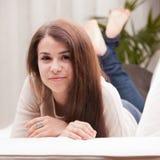 Självsäker härlig ung flicka på en soffa Royaltyfri Fotografi
