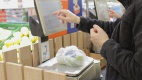Självservice i supermarket: mannen som använder vikt, graderar köpande nya frukter arkivfilmer