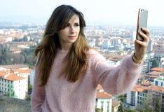 Självstående av den unga kvinnan med stadssikt Fotografering för Bildbyråer
