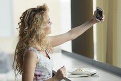 Självstående för ung blond flickadanande på hennes digitala kamera för smart telefon, medan sitta i kafé under lunchavbrott Royaltyfri Fotografi