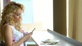Självstående för ung blond flickadanande på hennes digitala kamera för smart telefon, medan sitta i kafé under lunchavbrott stock video