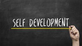 Självutvecklingsbegrepp Hand med gul text för inskrift för utveckling för markörhandstilsjälv på den svart tavlan arkivbild