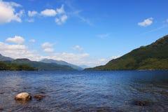 Sjö för landskapod-blått och blå himmel med moln i skotsk Skotska högländerna Royaltyfri Bild